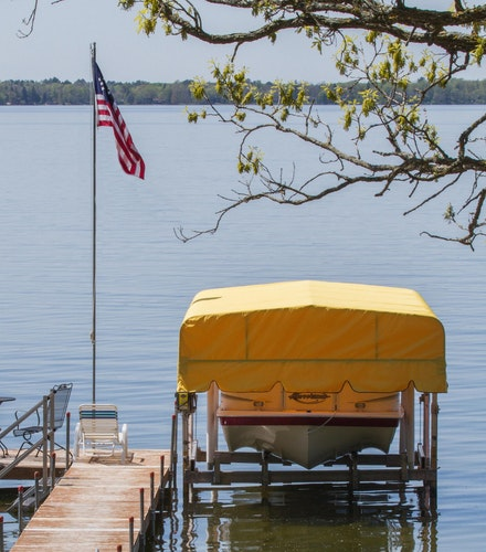 Boat Lift with Yellow Canopy Cover on Lake Beside US Flag
